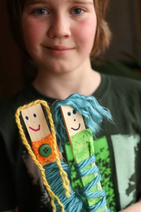 13. Paint Stick Dolls with Fabric Scraps and Yarns